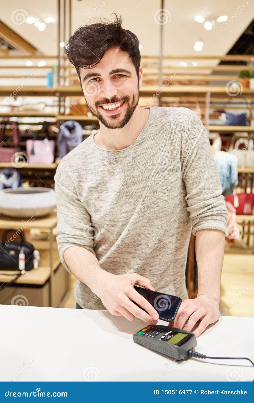Il giovane con il telefono cellulare effettua il pagamento mobile