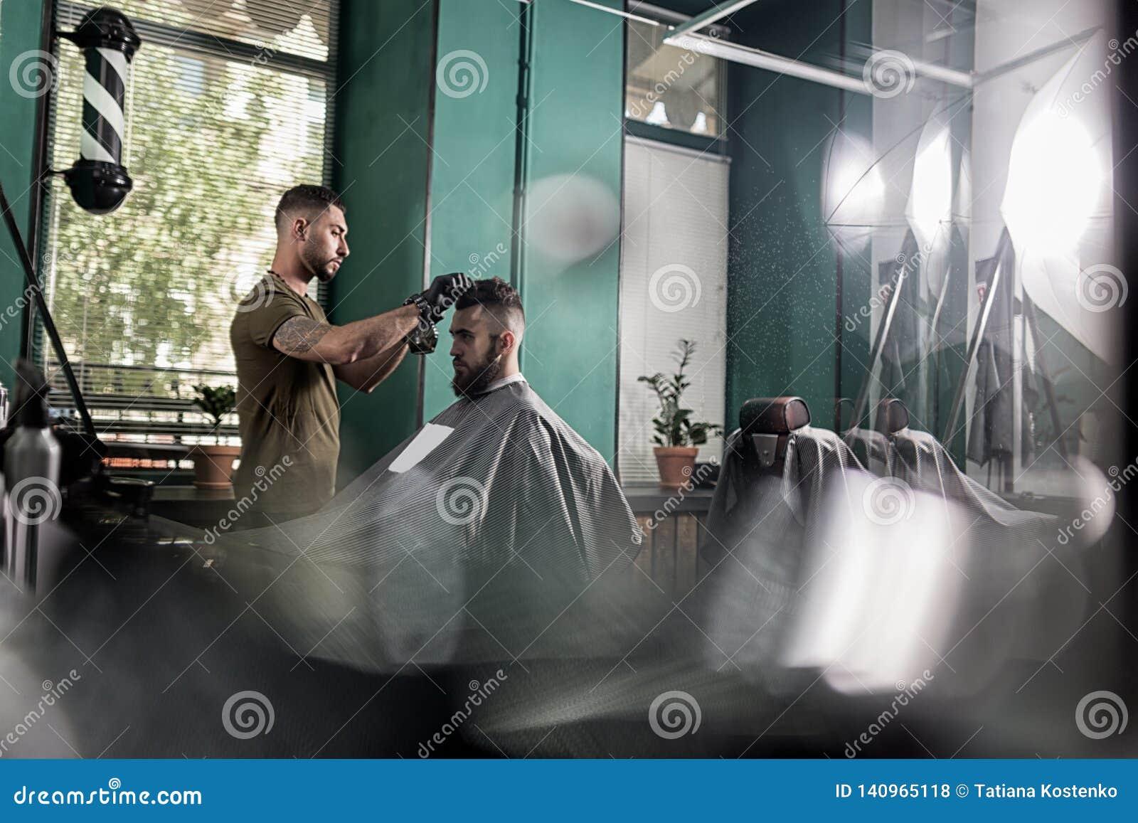 Il giovane con una barba si siede nella sedia ad un negozio di barbiere Il barbiere asciuga i capelli degli uomini