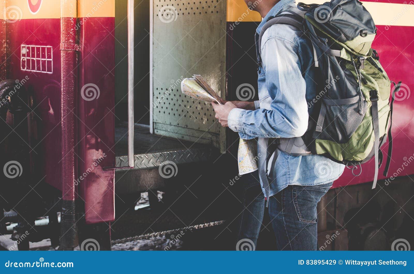 Il giovane entra in un treno internazionale solo con la mappa di viaggio su un binario nella stazione ferroviaria