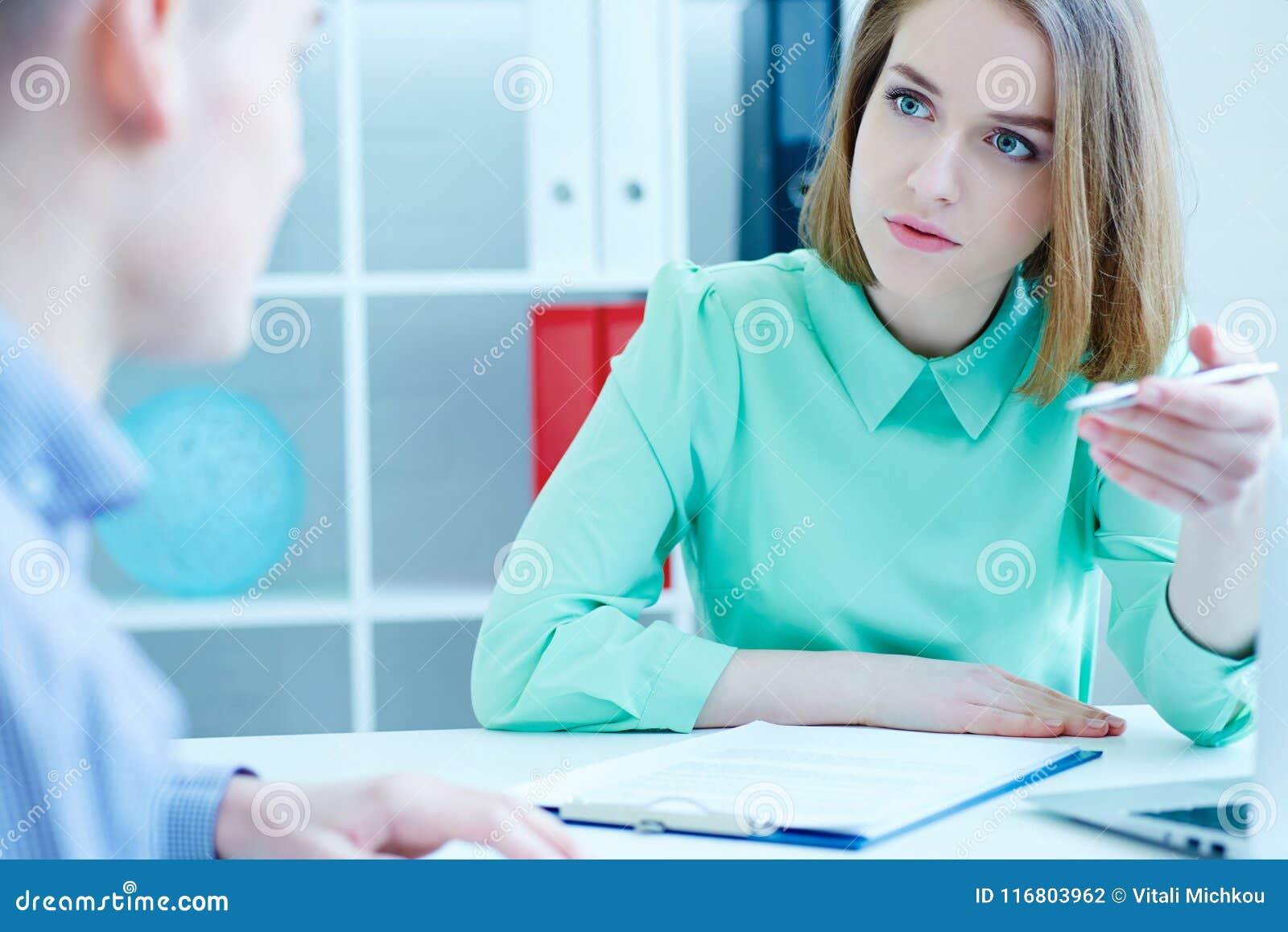 Il giovane impiegato femminile dell agenzia di assunzione di personale contribuisce a compilare la forma al cercatore di lavoro m