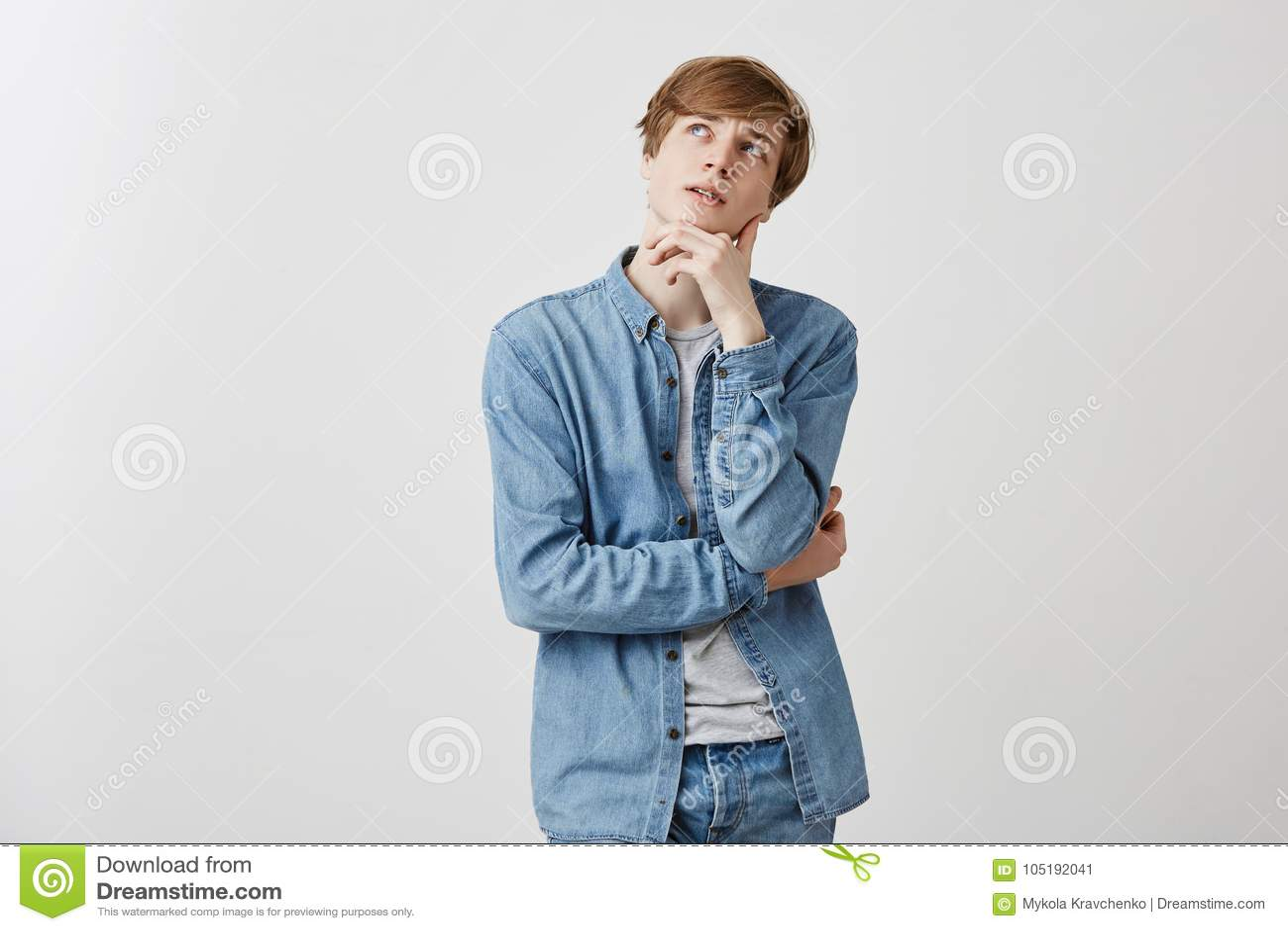 Il giovane maschio sembrante piacevole pensieroso con capelli giusti e gli occhi azzurri in jeans indossano, tiene la mano sotto