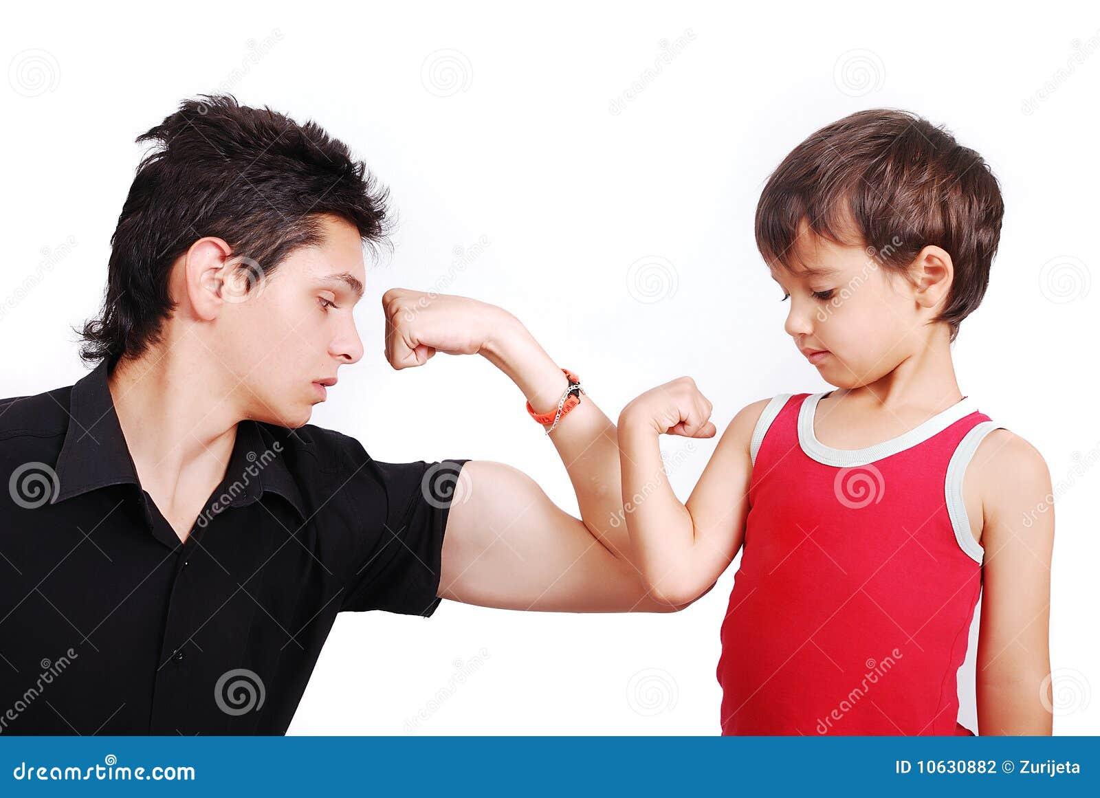 Il giovane modello maschio sta mostrando i muscoli al ragazzino
