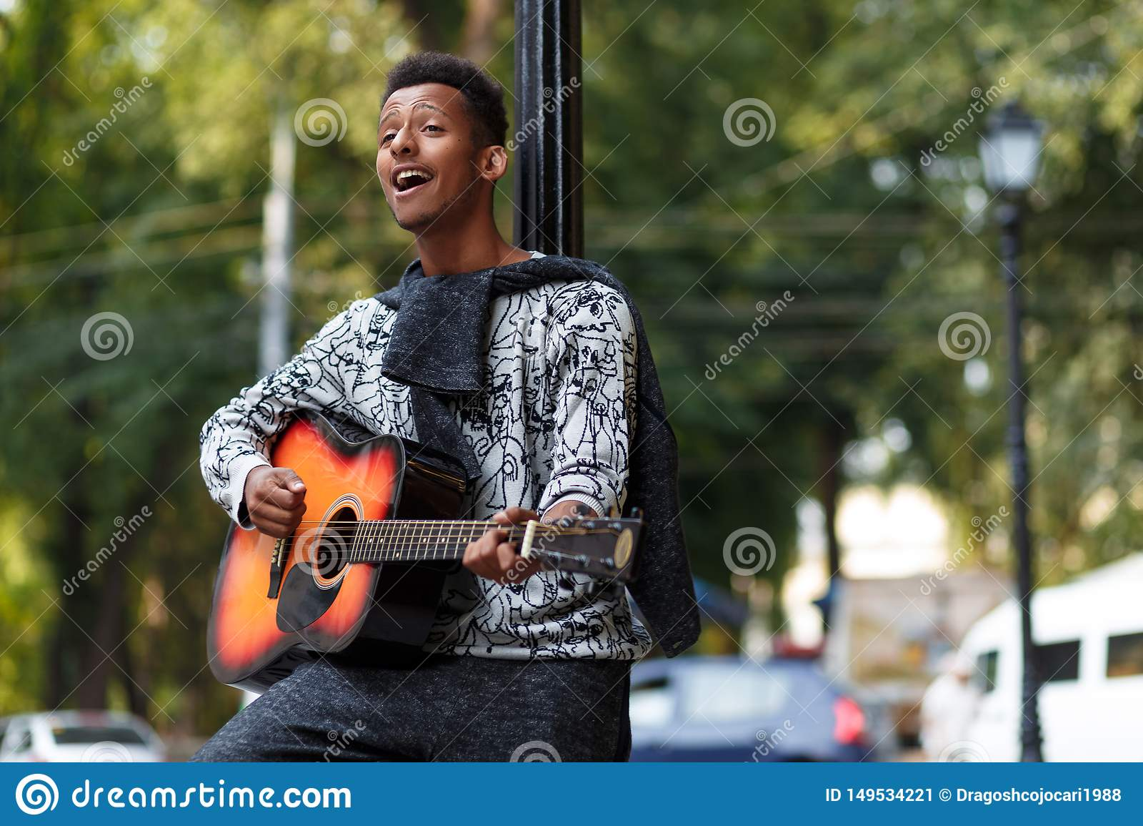 Il giovane musicista giocato sulla chitarra, canta una canzone nel giorno soleggiato, su un fondo vago della via