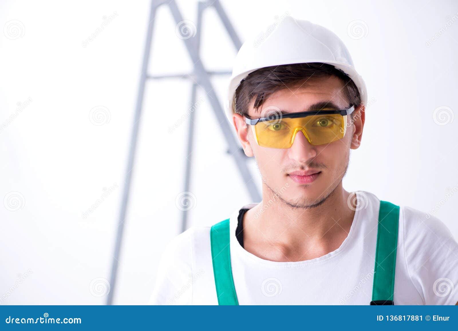 Il giovane operaio con attrezzatura protettiva nel concetto di sicurezza
