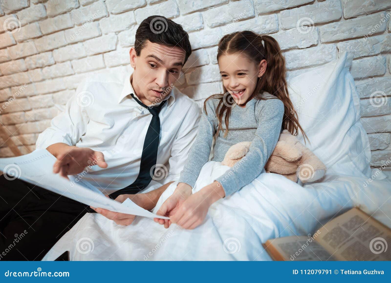 Il giovane padre dice sua figlia circa il suo lavoro L uomo d affari mostra la piccola figlia lui fa