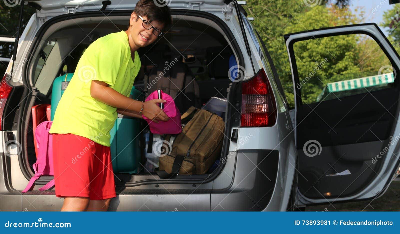 Il giovane ragazzo con i vetri ha caricato i bagagli nel tronco
