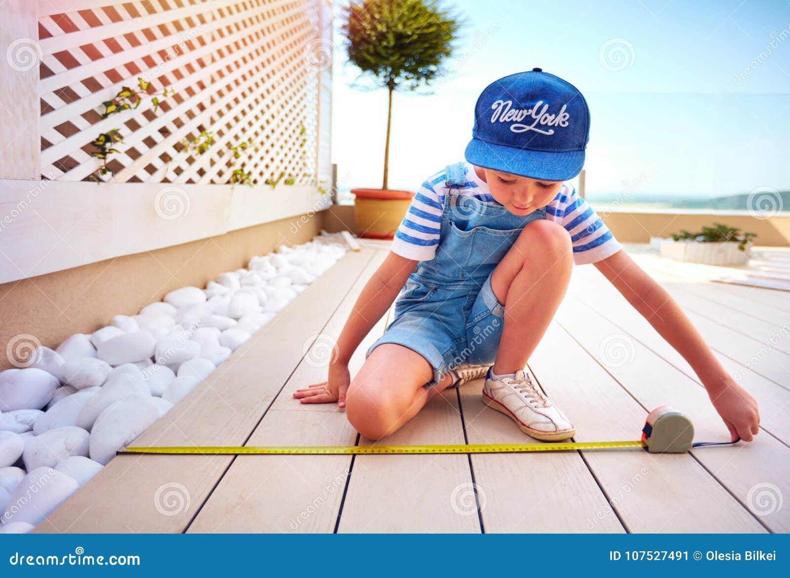 Il giovane ragazzo sveglio, bambino aiuta il padre con il rinnovamento della zona del patio del tetto