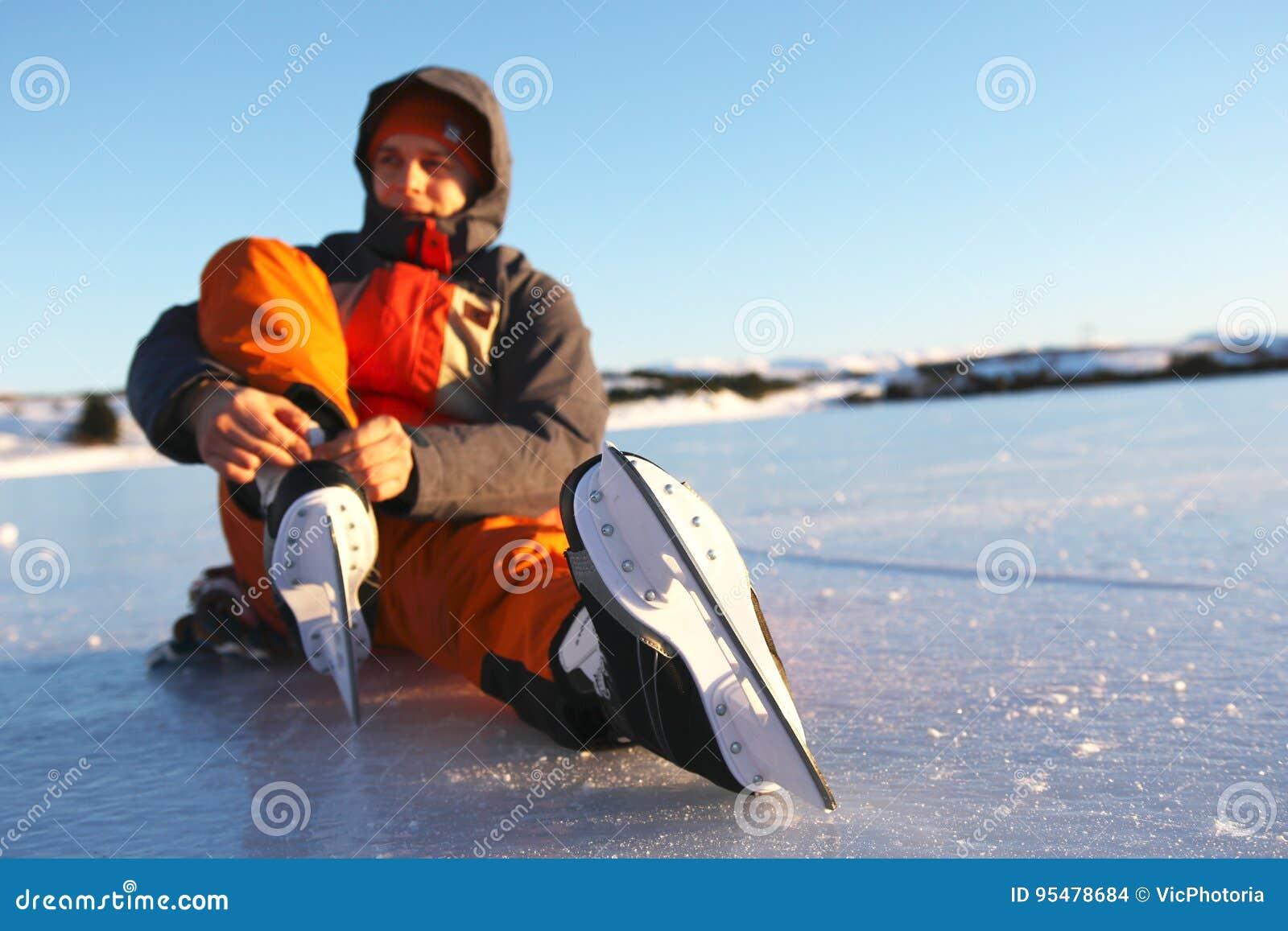 Il giovane si siede sul ghiaccio che stringe i laccetti sui suoi pattini da ghiaccio
