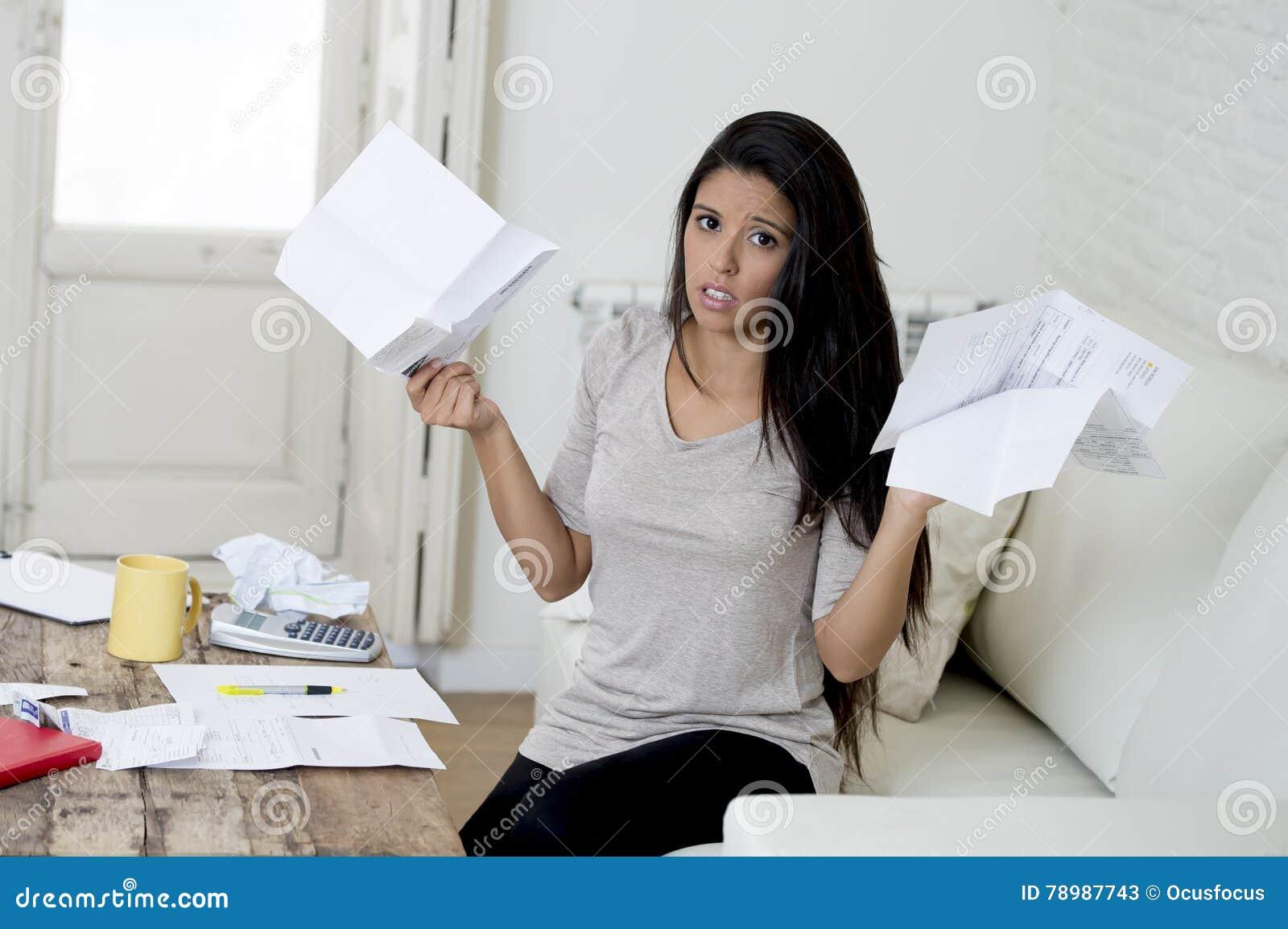 Il giovane strato latino attraente del salone della donna a casa che calcola le spese mensili si è preoccupato nello sforzo
