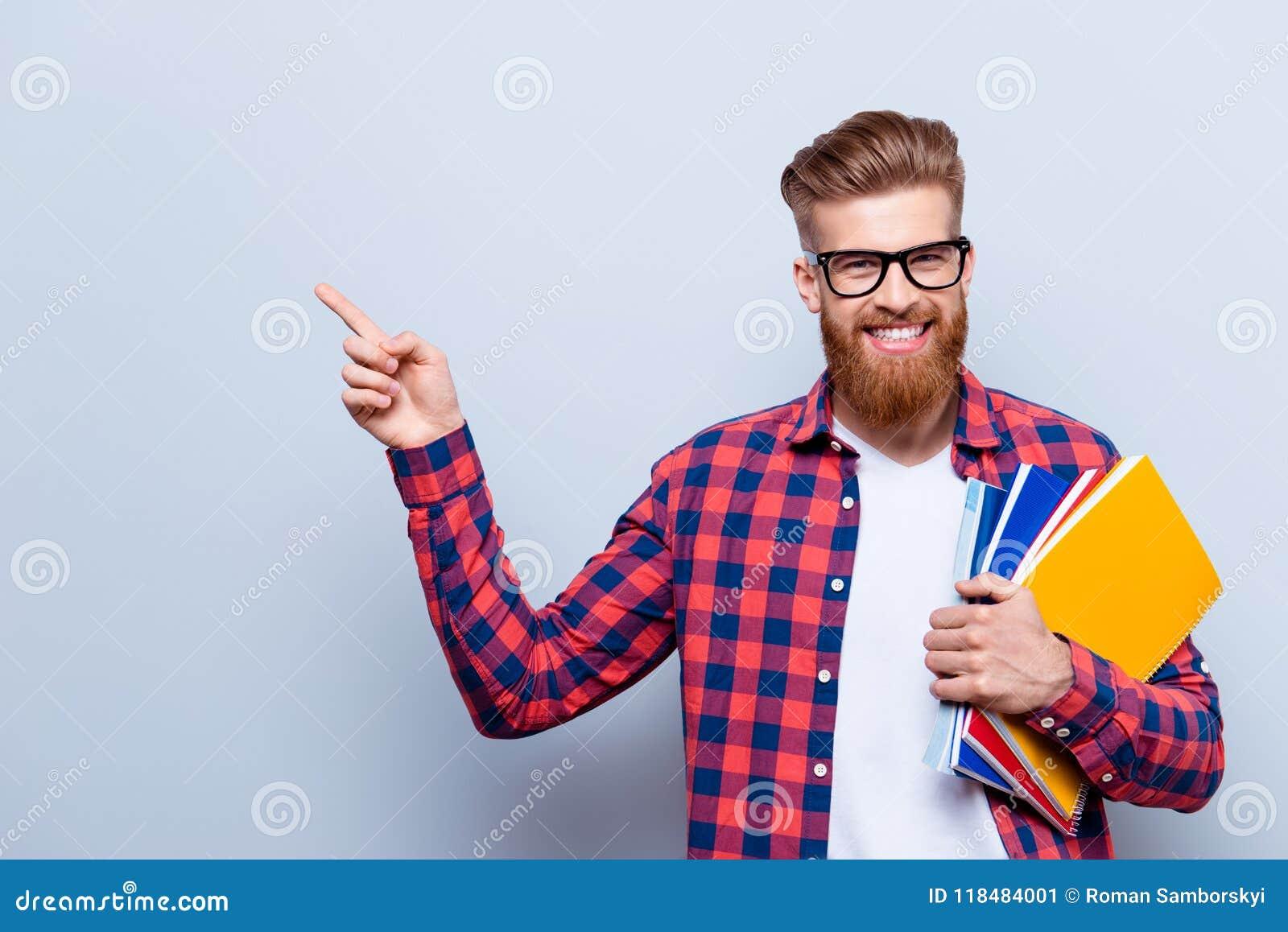 Il giovane studente alla moda barbuto rosso nerd sorridente sta stando con