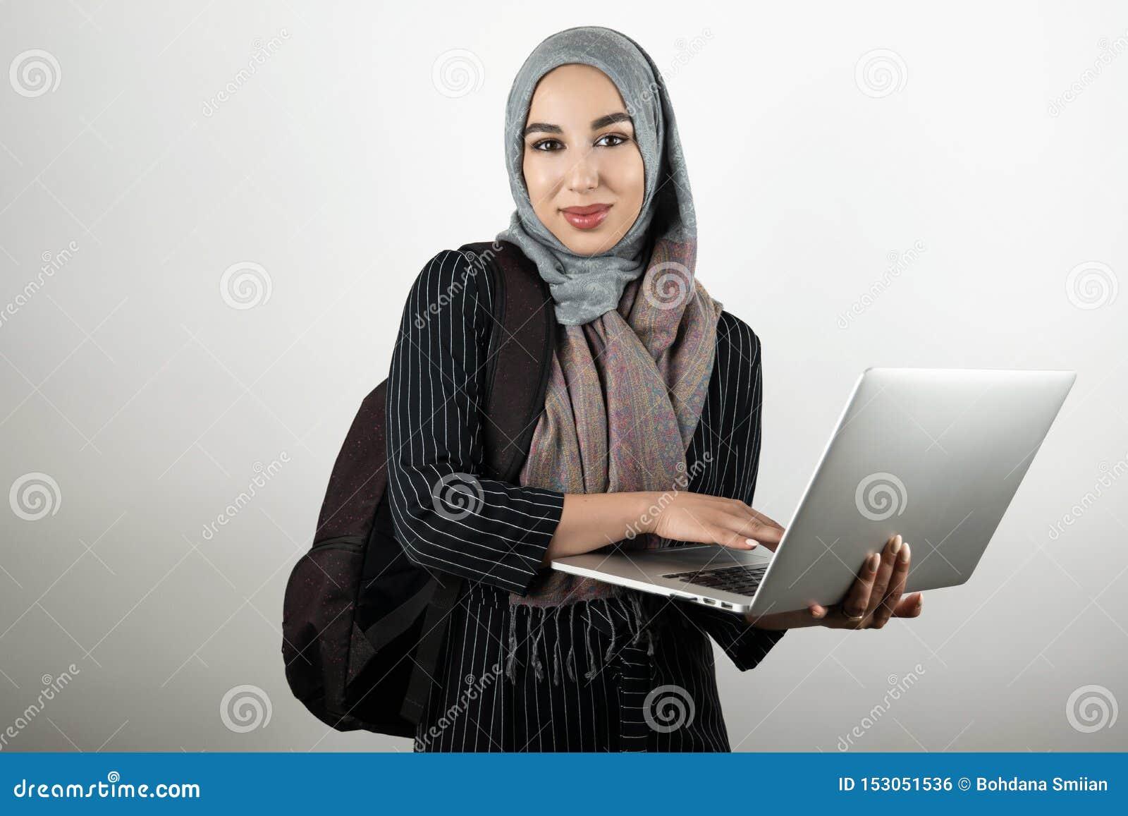 Il giovane studente musulmano attraente con bagpack che tiene e che spilla il suo foulard d uso del hijab del turbante del comput