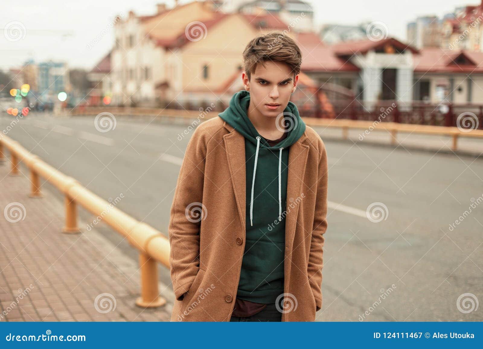 Il giovane tipo alla moda in un cappotto d avanguardia con una maglia con cappuccio cammina