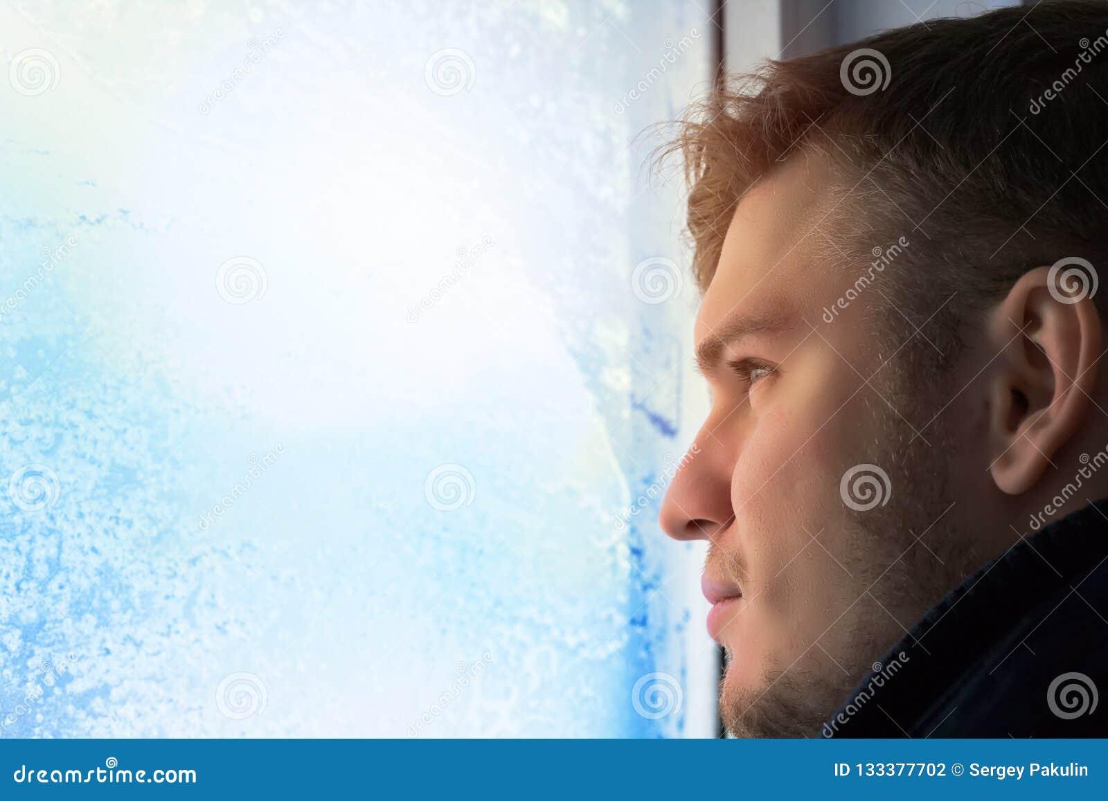 Il giovane uomo attraente nel giorno di inverno guarda fuori la finestra Vetro in brina e fiocchi di neve Ritratto del primo pian