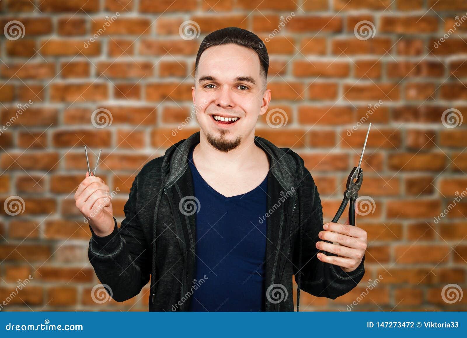 Il giovane uomo barbuto tiene la bulletta per suole e le pinze sul fondo del muro di mattoni