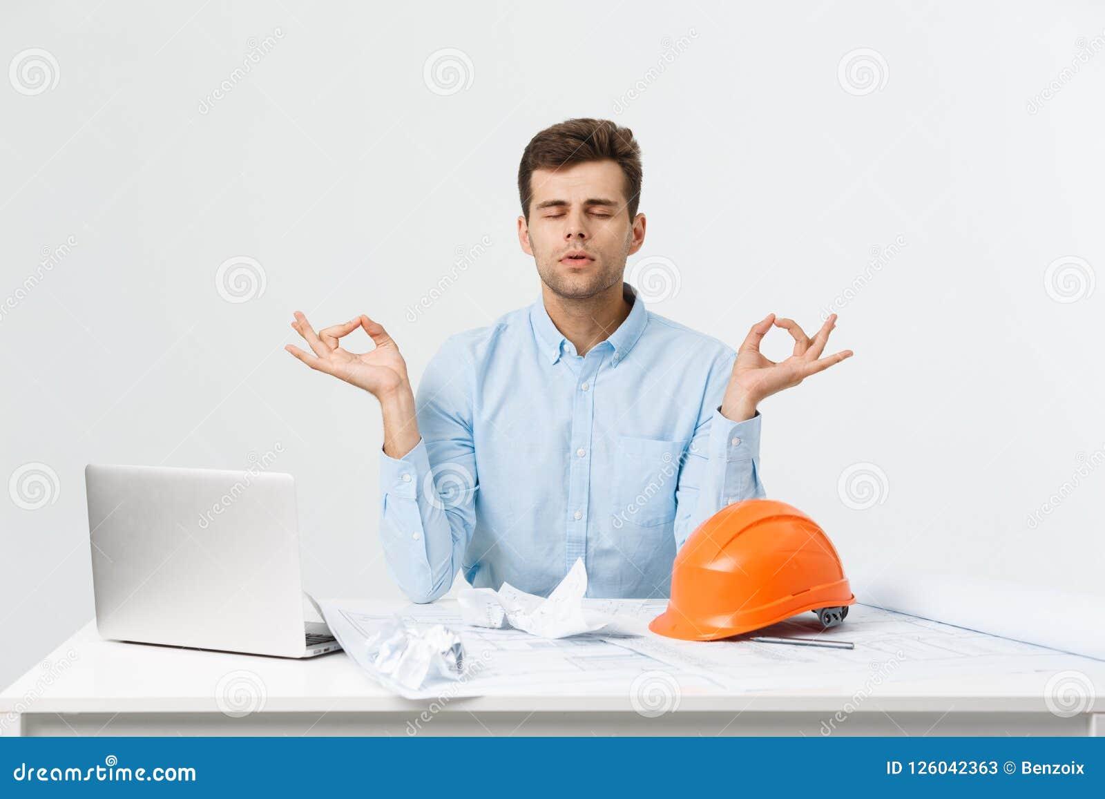 Il giovane uomo bello del costruttore o dell ingegnere nell yoga blu di pratica del vestito e si rilassa alla stanza dell ufficio