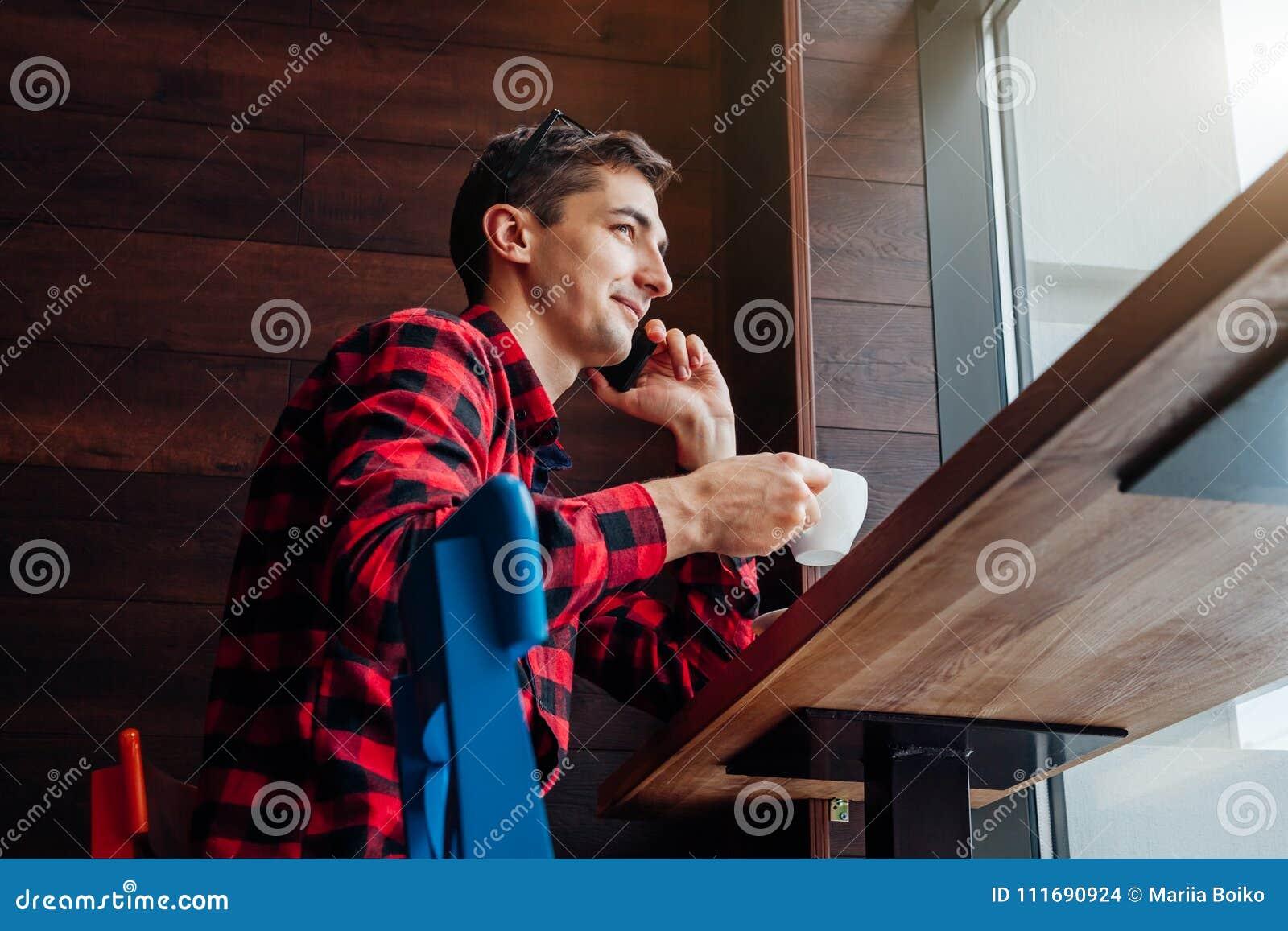 Il giovane uomo bello gode del caffè nel caffè