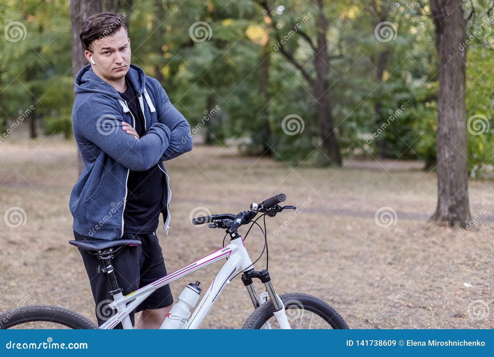 Il giovane uomo caucasico bello sta le mani attraversate con la bicicletta che aggrotta le sopracciglia e serio Cuffie senza fili