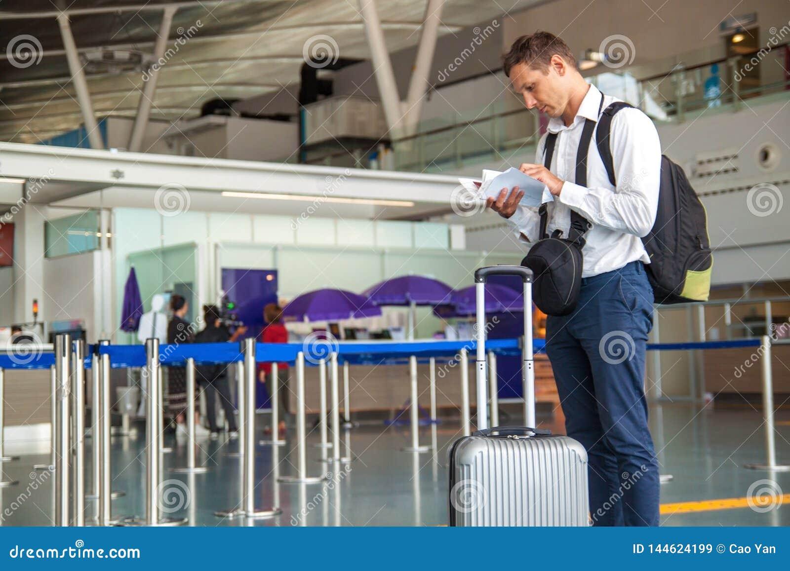 Il giovane uomo d affari bello in camicia bianca che allunga fuori il suo biglietto mentre sta davanti alla linea aerea controlla