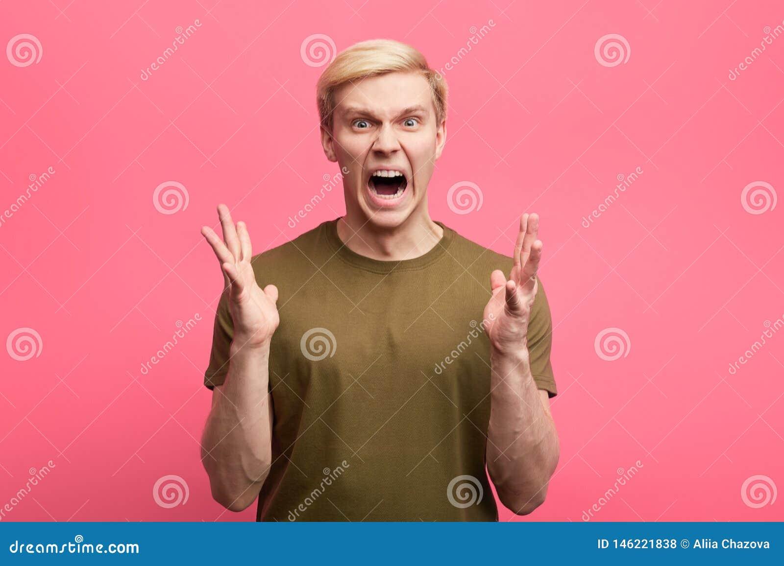 Il giovane uomo emozionale con l espressione aggressiva e le armi si sono alzati