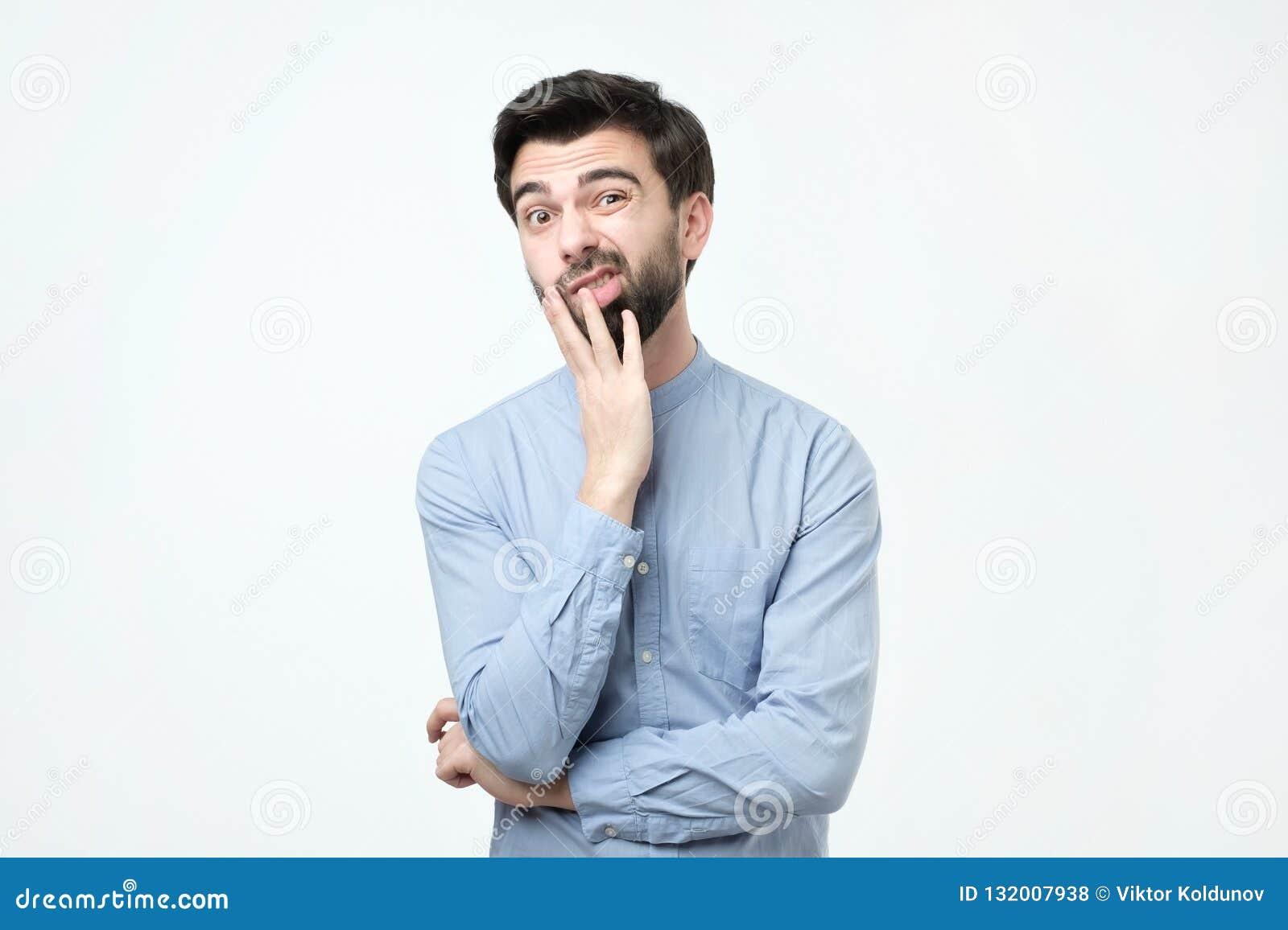 Il giovane uomo europeo in camicia blu pensa, guarda da parte a parte incredulously