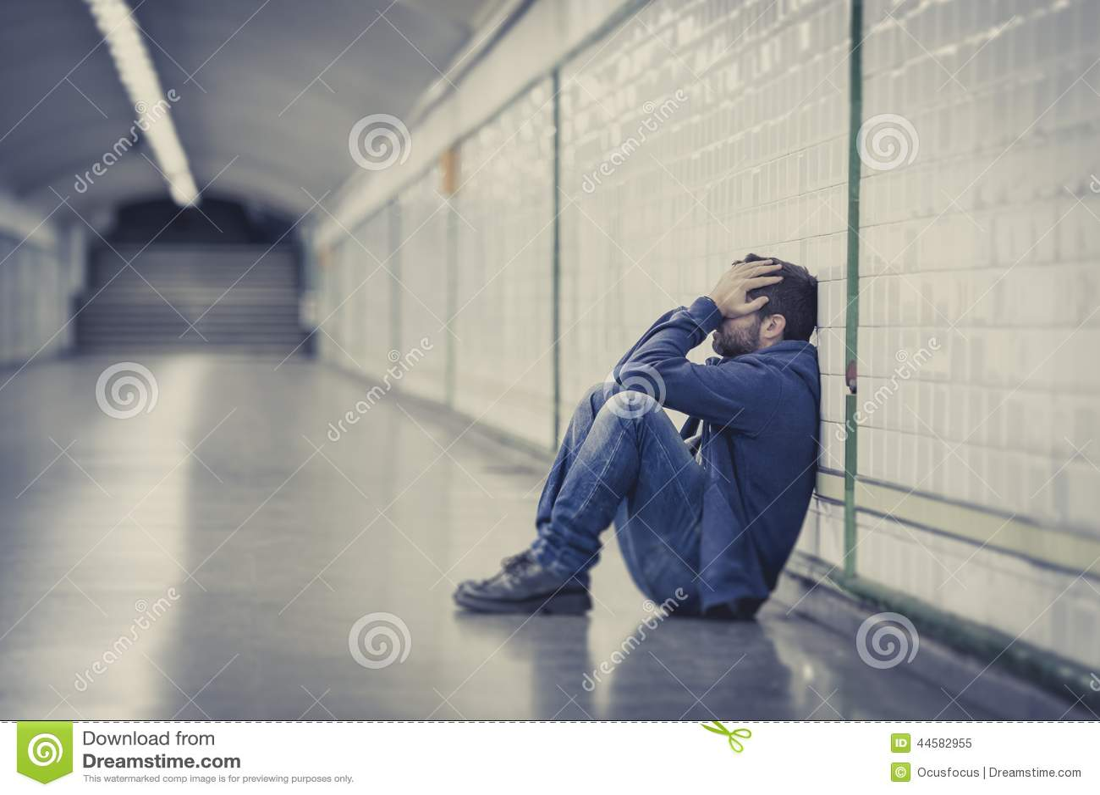 Il giovane uomo malato ha perso la depressione di sofferenza che si siede sul tunnel a terra del sottopassaggio della via