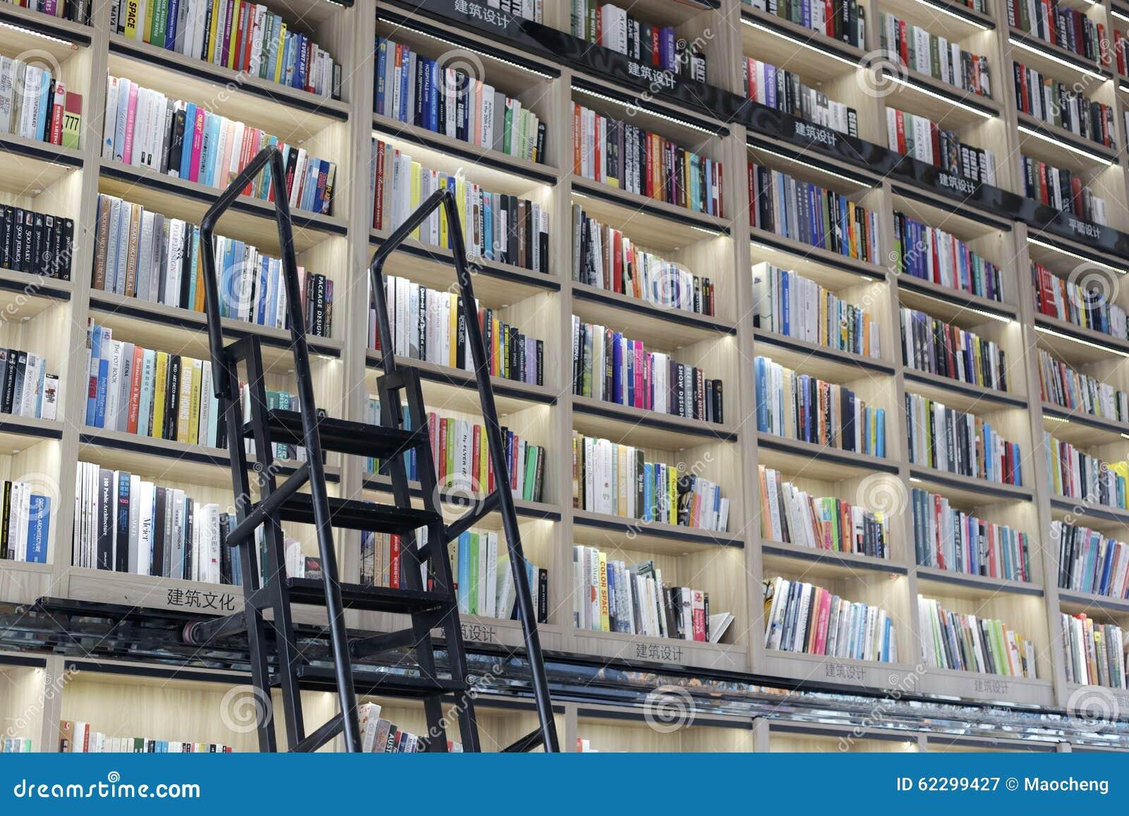 Il grande scaffale per libri con la scala del ferro del deposito