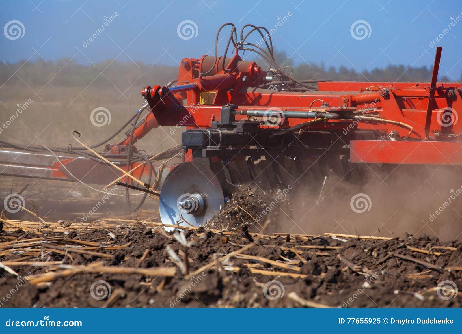 Il grande trattore che tira un aratro ed ara il campo, rimuove i resti del girasole precedentemente smussato
