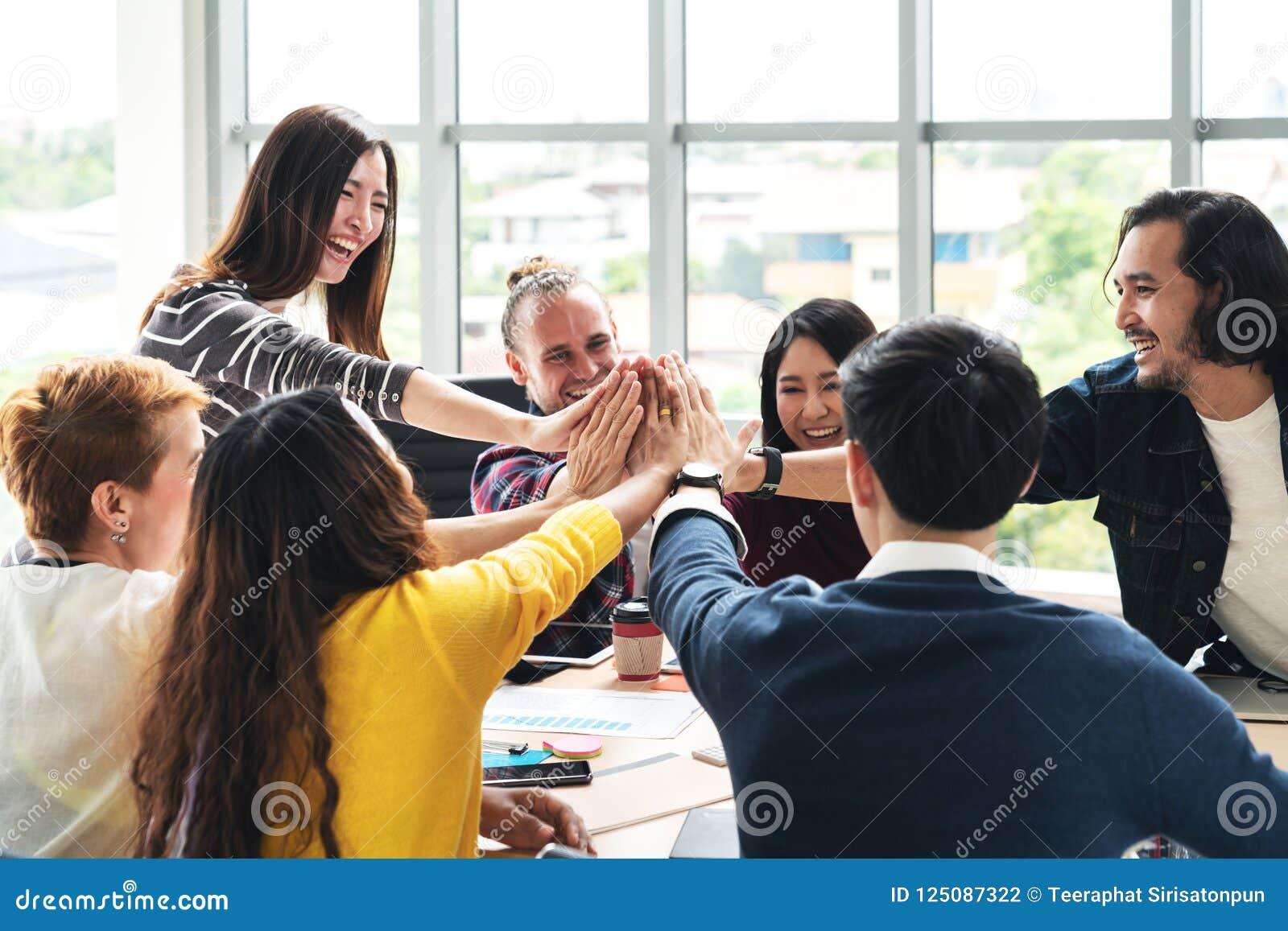 Il gruppo di diversi giovani multietnici gesture la mano su cinque, ridendo e sorridendo insieme nella riunione di lampo di genio