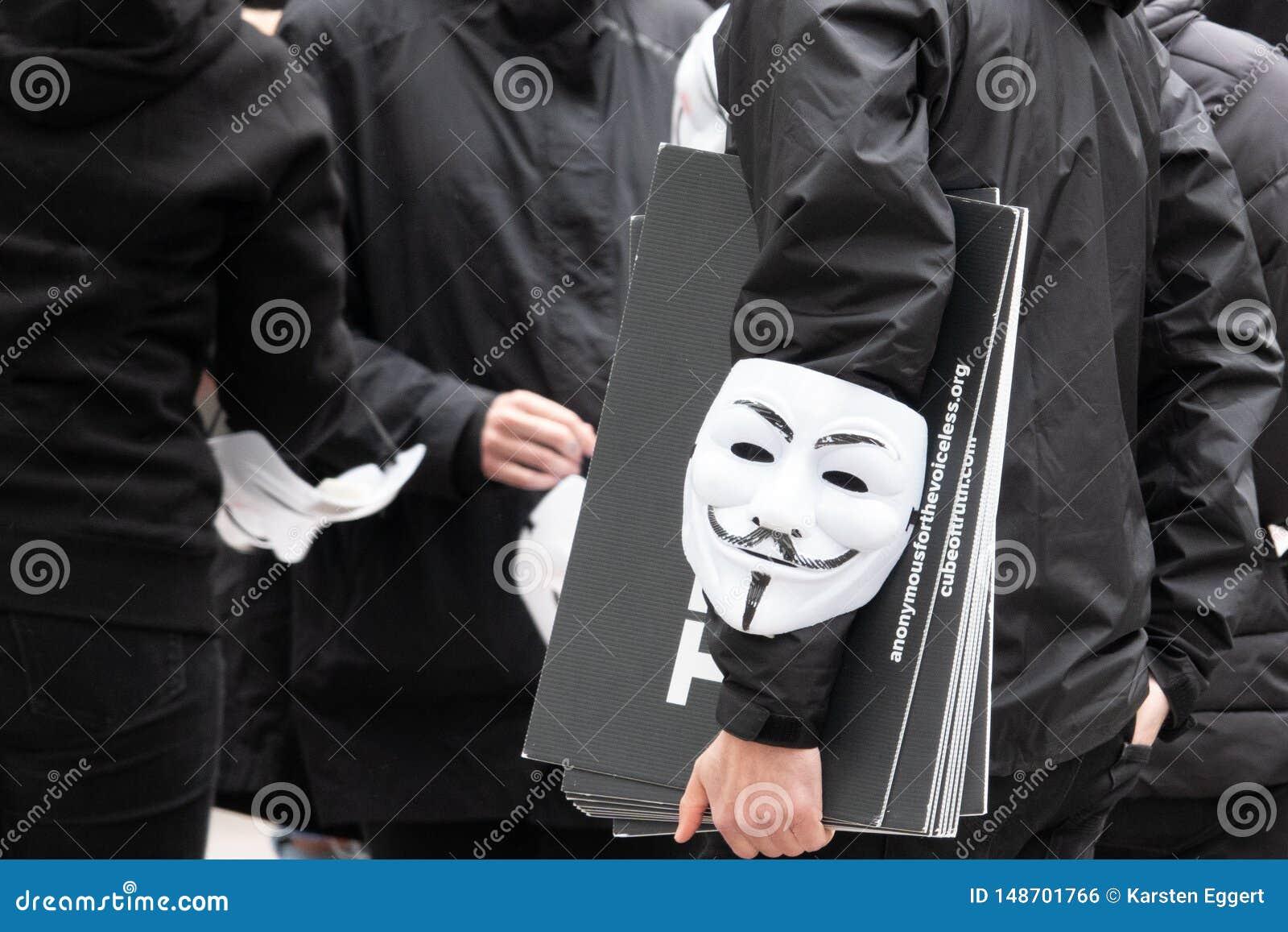 Il gruppo di giovani vestiti tutti nel nero esce sulla via dimostrare con le maschere anonime