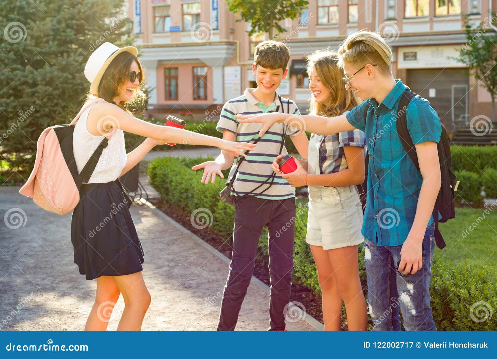 Il gruppo di gioventù sta divertendosi, amici felici degli adolescenti che camminano, parlante godendo del giorno nella città