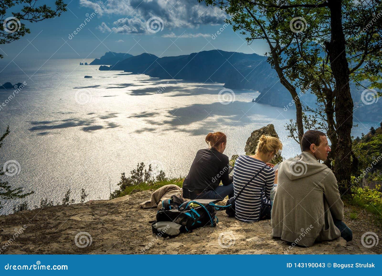 Il gruppo di viandanti che riposano sul percorso dei trascina su costo di Amalfi, Italia