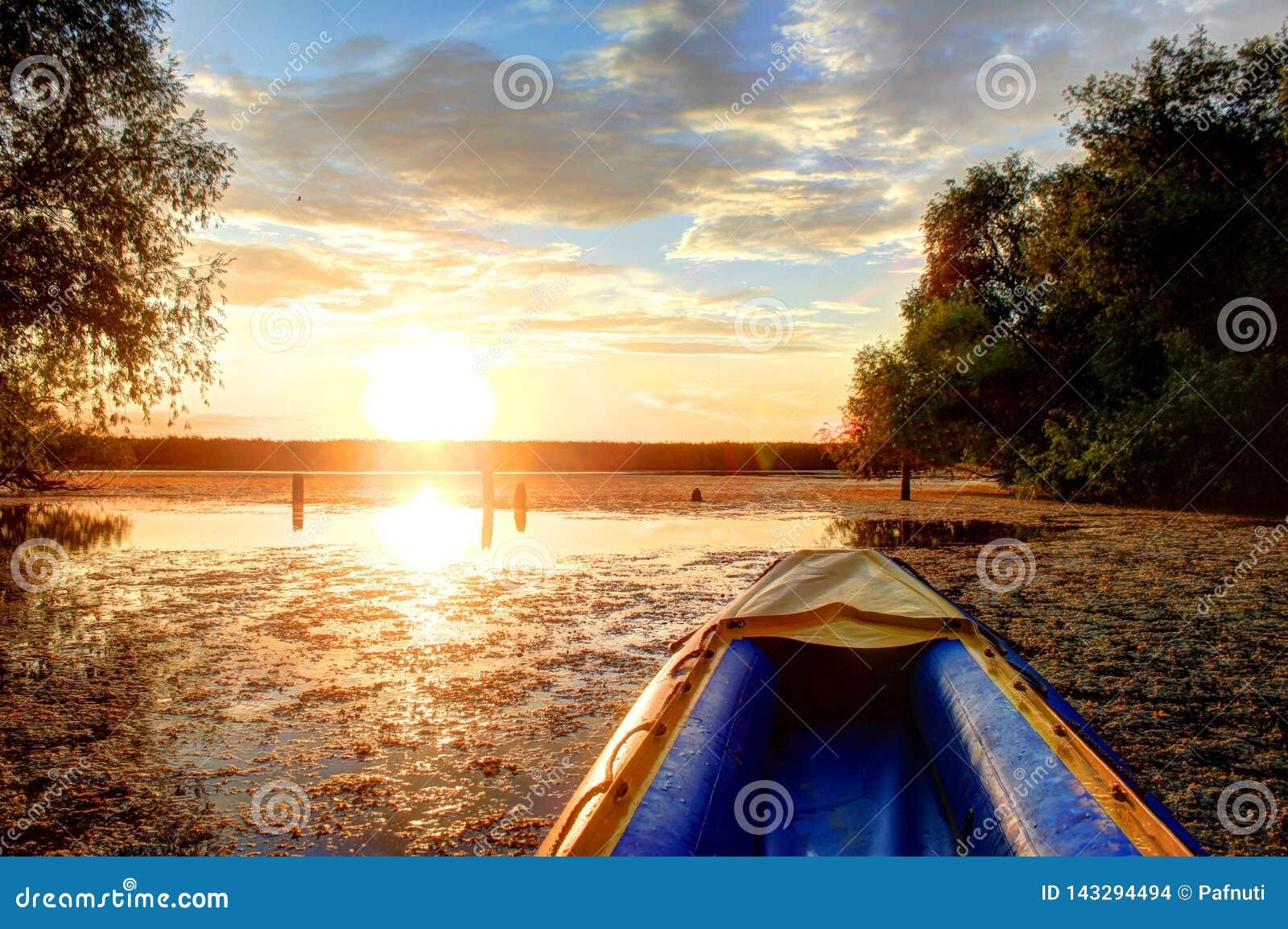 Il kajak blu contro il tramonto navigherà a valle