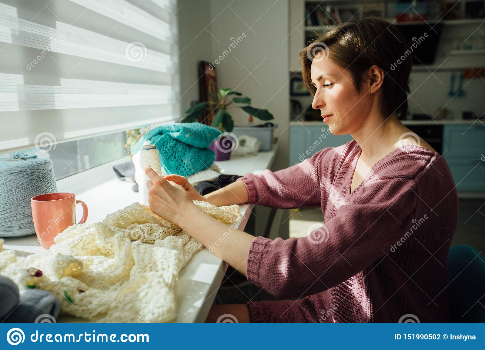 Il lato della donna che tricotta il vestito tenero con lavora all uncinetto Lavoro creativo delle free lance femminili nel luogo