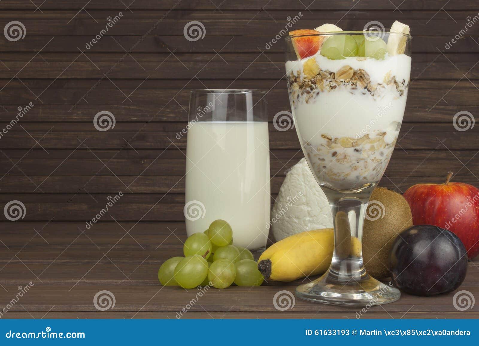 Il latte fresco nel vetro ed i muesli fanno colazione su una tavola di legno Farina d avena con latte e cagliata, pasti per gli a