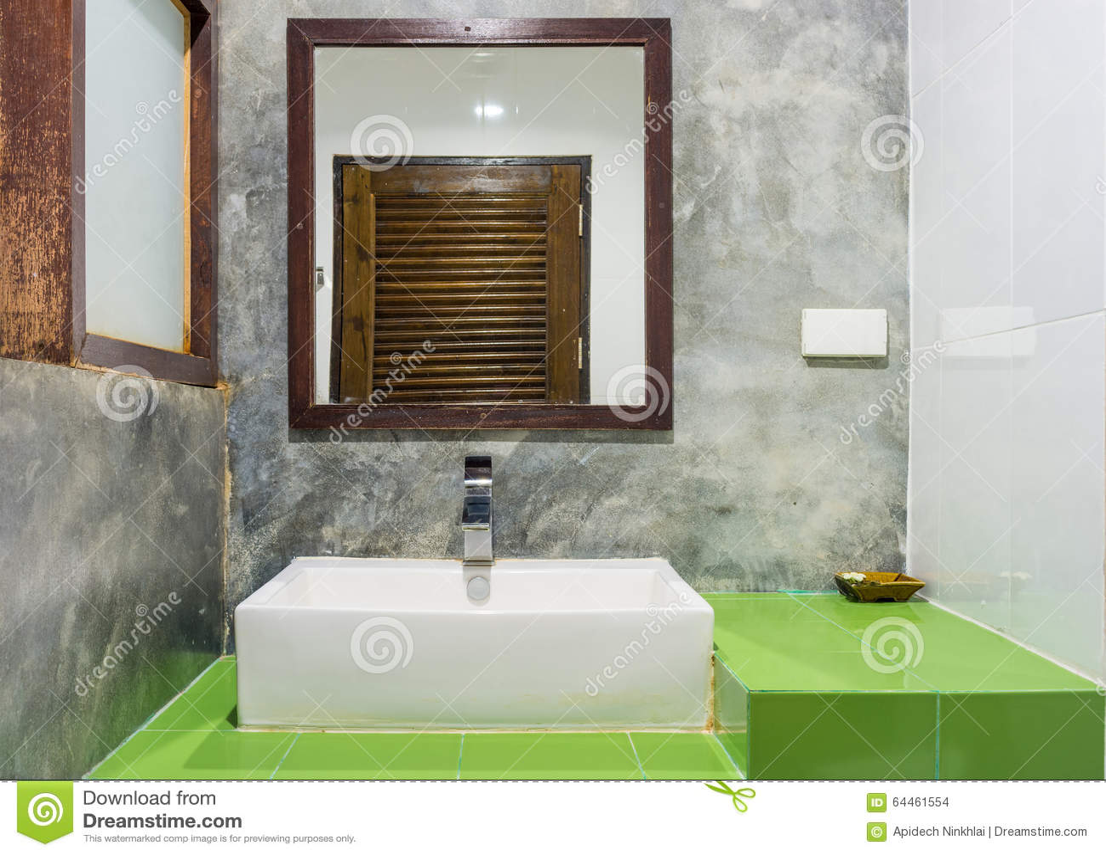 Il lavandino la ciotola e lo specchio ceramici sulle piastrelle