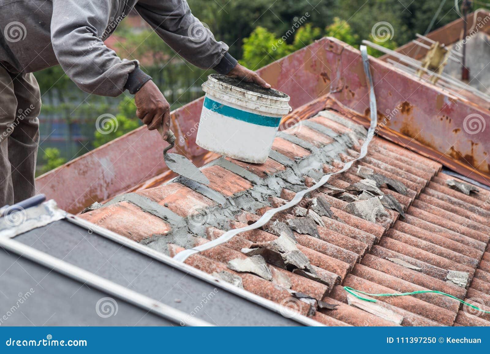 Costruire Tetto In Cemento il lavoratore asiatico fissa le mattonelle di tetto con