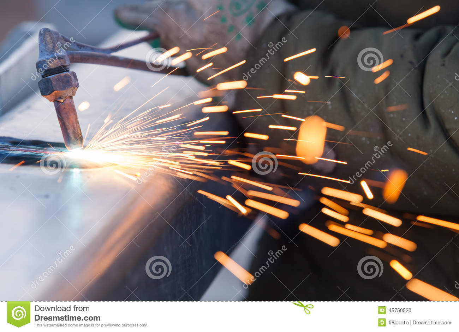 Il lavoratore che taglia il tubo d acciaio facendo uso della torcia del metallo ed installa il bordo della strada