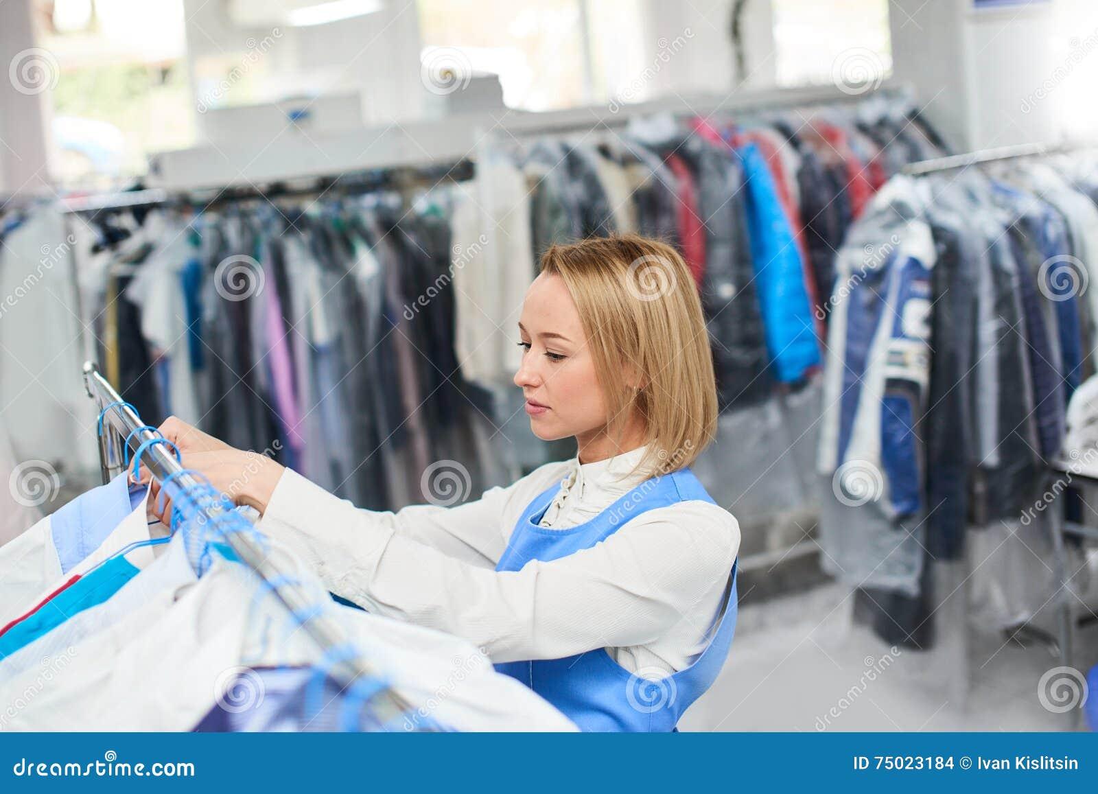 Il lavoratore della ragazza appende i vestiti puliti della lavanderia su un gancio