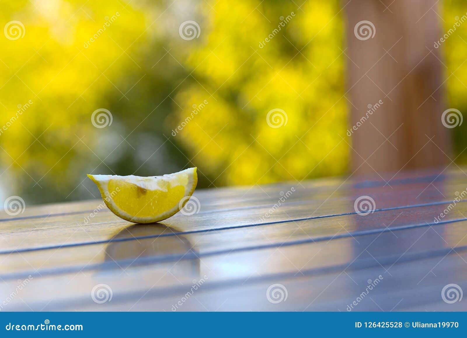 Il limone del taglio pieve sulla tavola di legno del caffè sul fondo verde dell estate