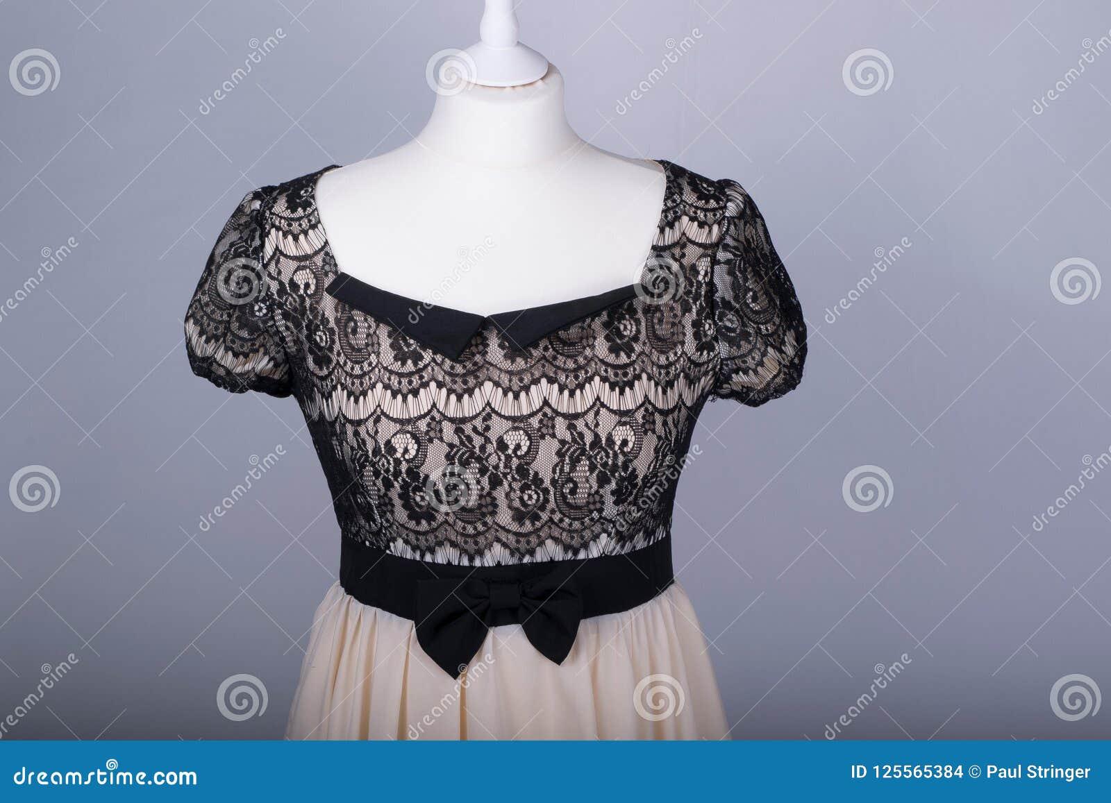 57b8230bd389 Il manichino dei sarti si è vestito in un vestito beige e nero dal pizzo