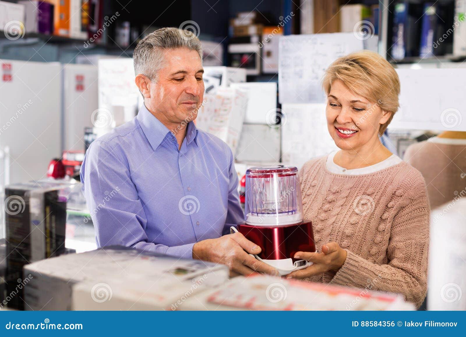 Il marito e la moglie in negozio degli elettrodomestici scelgono gli spremiagrumi
