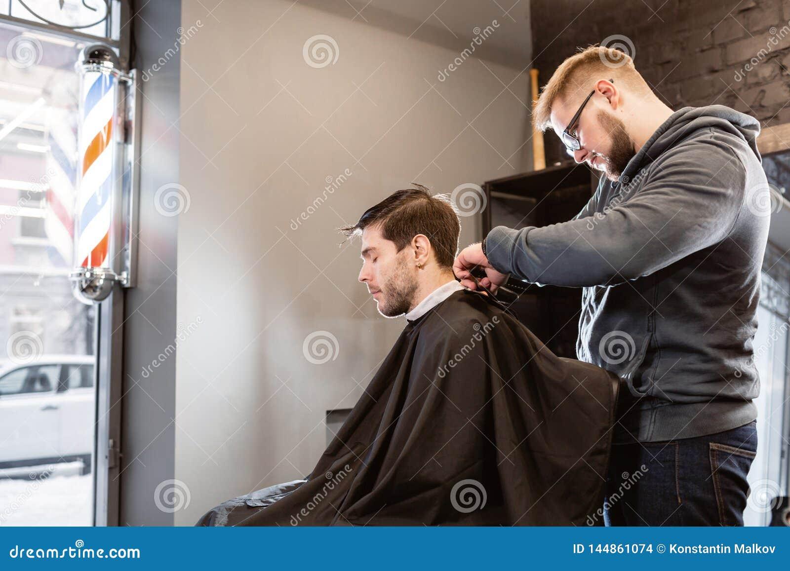 Il Master taglia i capelli e la barba degli uomini nel parrucchiere, parrucchiere fa l acconciatura per un giovane Lavoro del bar