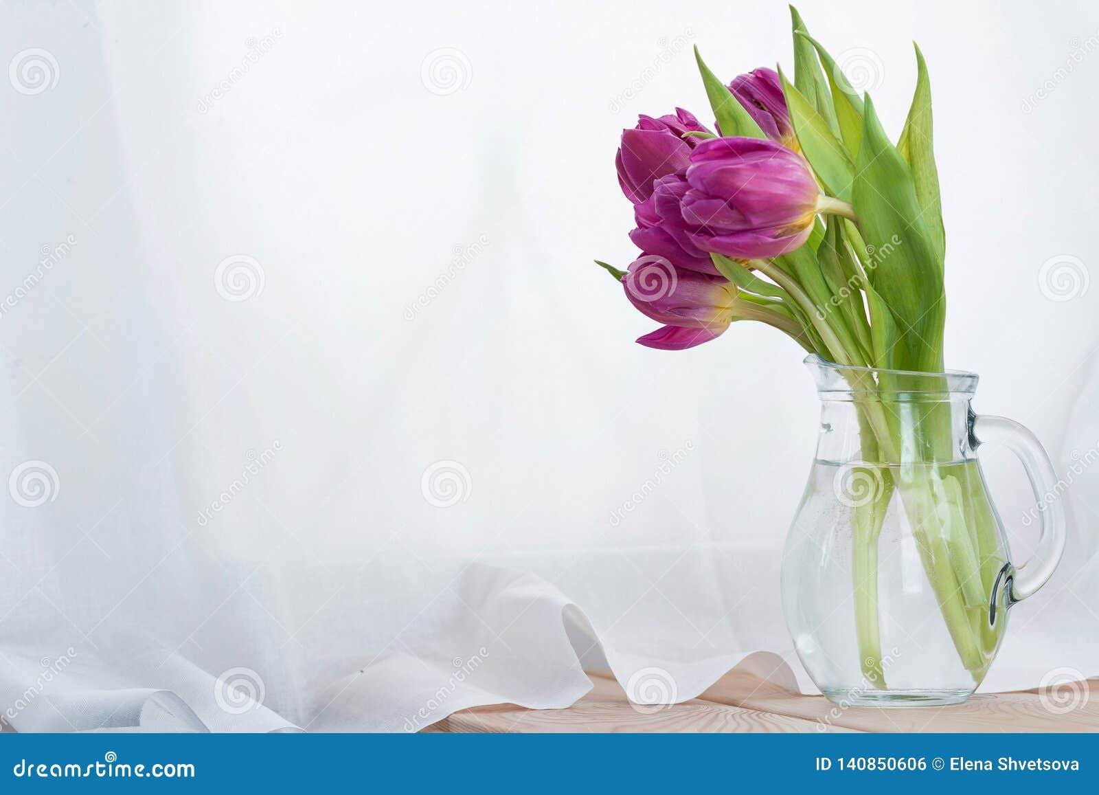 Il mazzo dei tulipani rosa in un decantatore di vetro su una tavola di legno