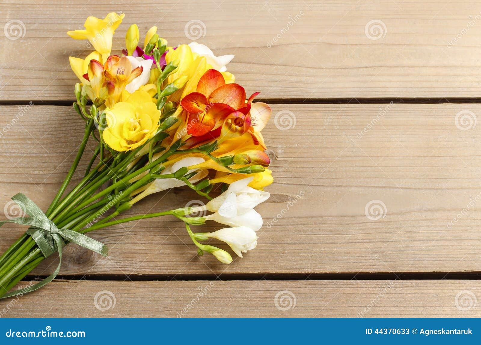 Il mazzo di fresia variopinta fiorisce su legno marrone