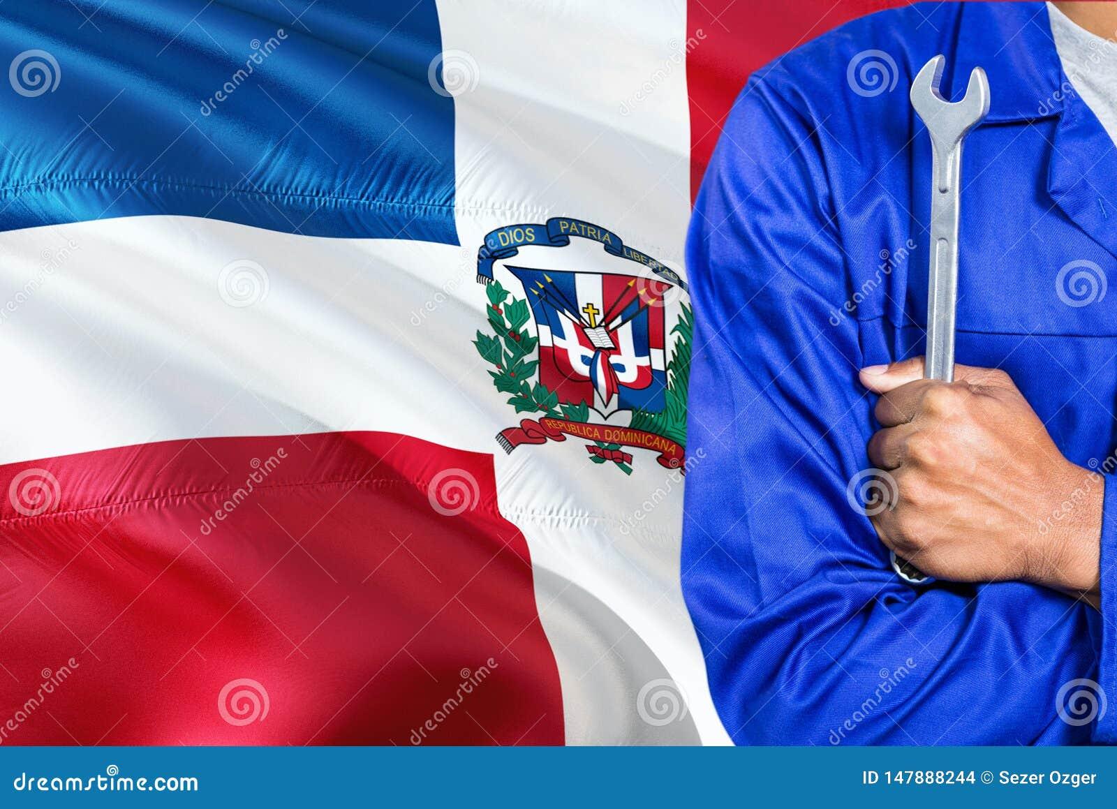 Il meccanico domenicano in uniforme blu sta tenendo la chiave contro l ondeggiamento del fondo della bandiera della Repubblica do