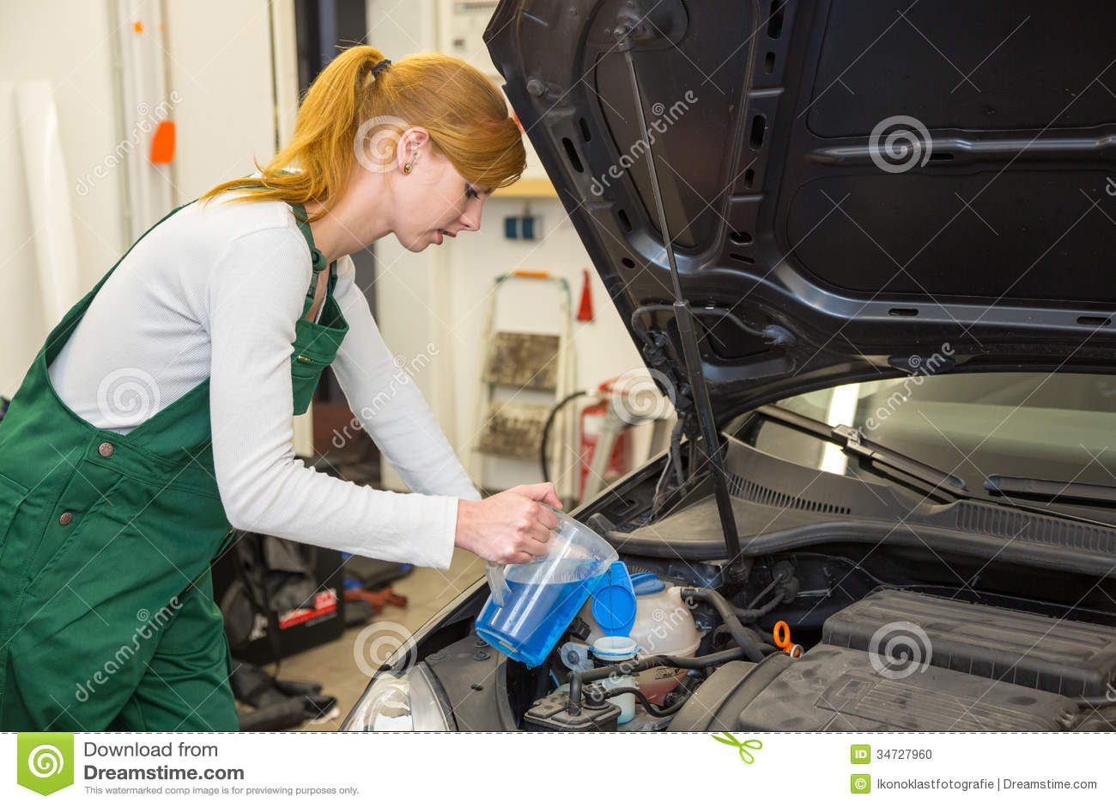 Il meccanico femminile riempie il liquido refrigerante o il liquido di raffreddamento in motore di un automobile