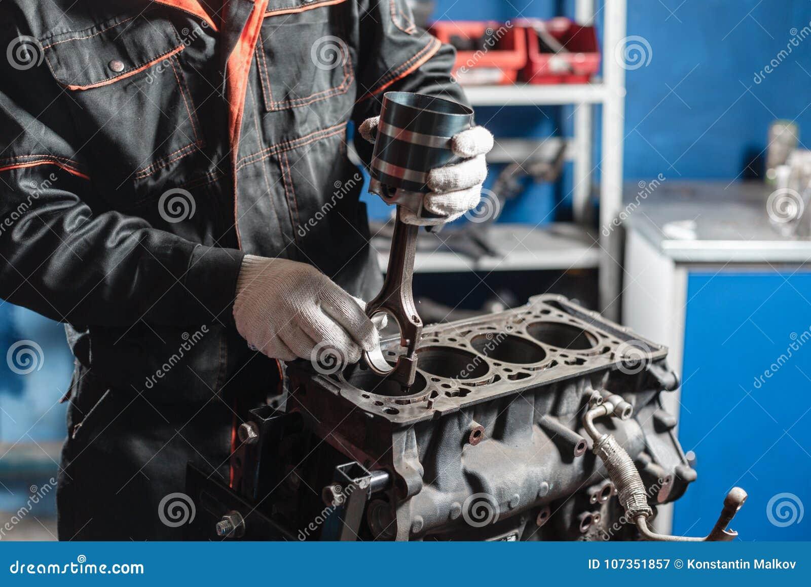 Il meccanico installa un nuovo pistone Smonti il veicolo del blocco motore Riparazione del capitale del motore Sedici valvole e q