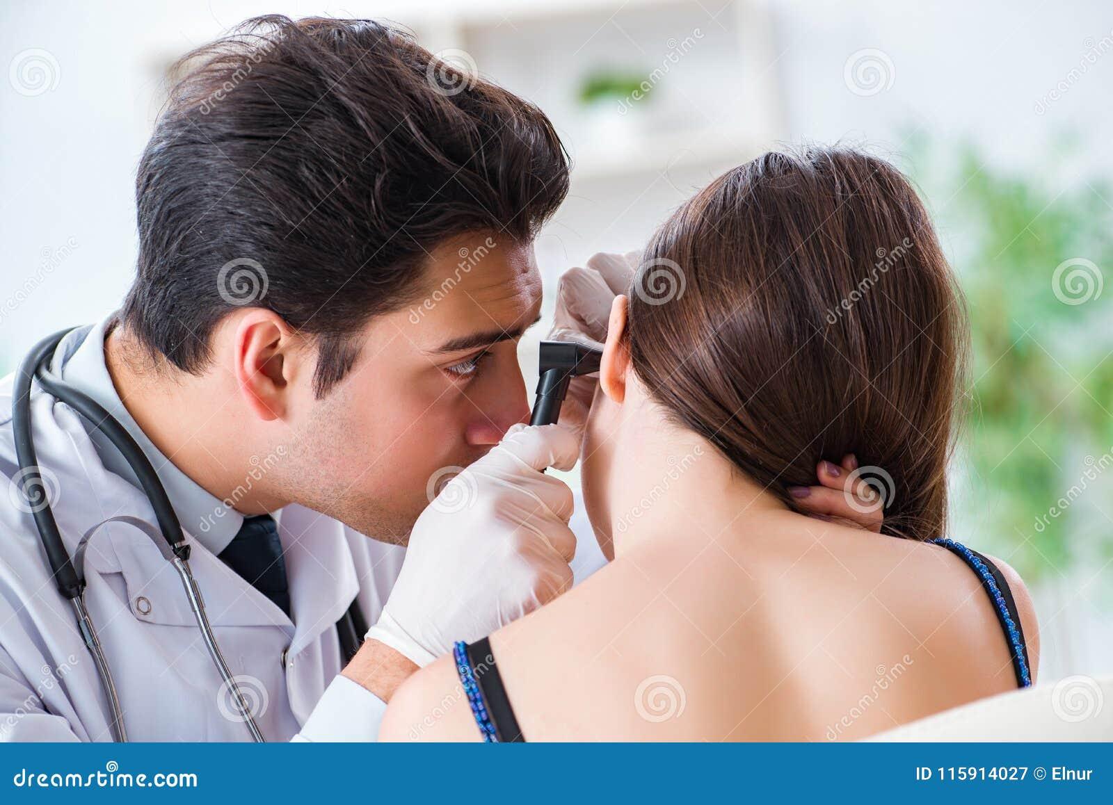 Il medico che controlla l orecchio dei pazienti durante l esame medico
