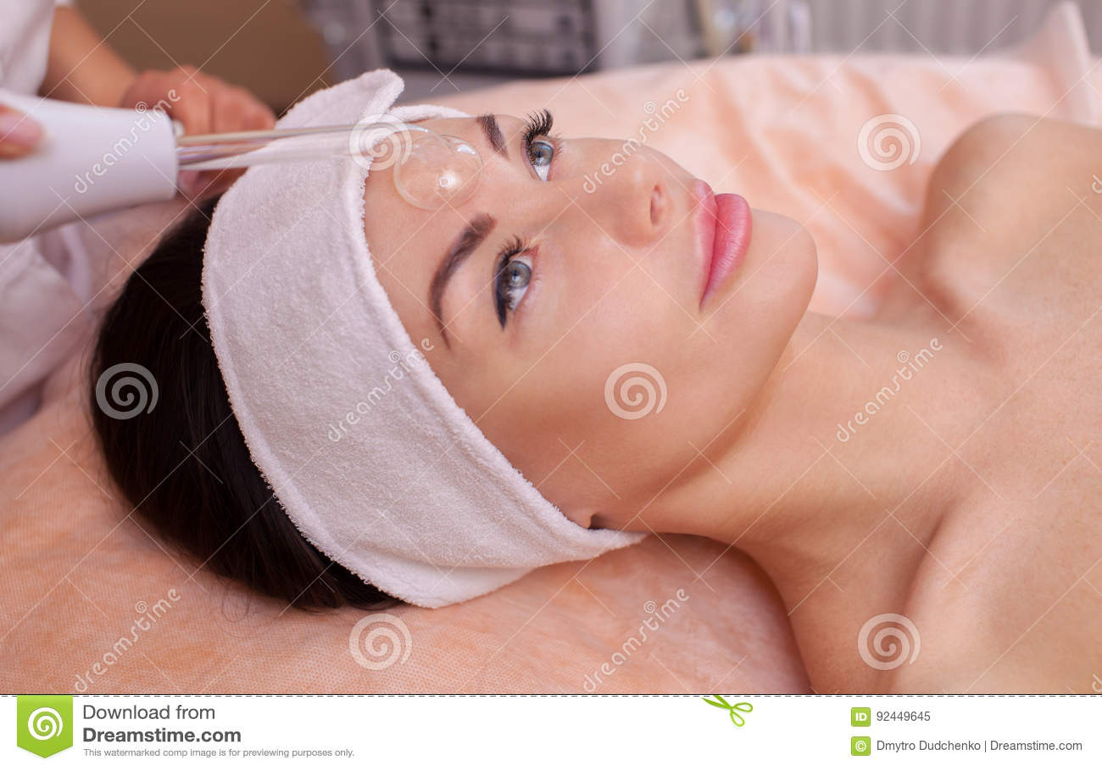 Il medico-cosmetologo fa la terapia di Microcurrent di procedura della pelle facciale sulla fronte