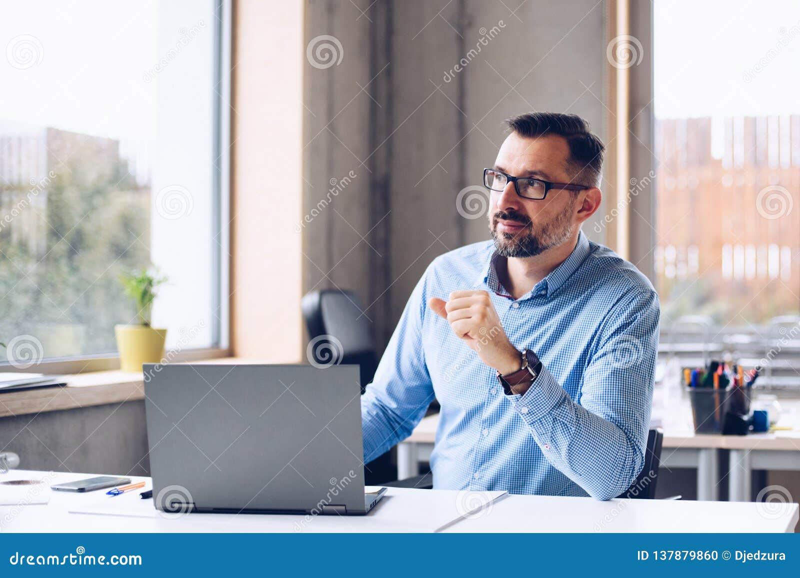 Il mezzo ha invecchiato l uomo bello nel funzionamento della camicia sul computer portatile in ufficio